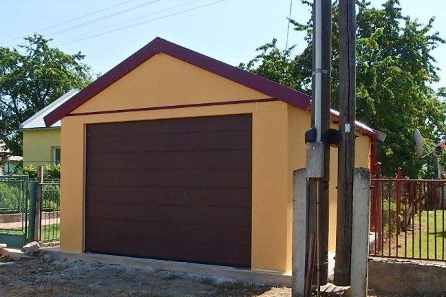 Eine gelbe Satteldach-Garage mit braunem Sektionaltor von Hörmann