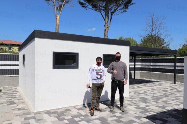 Ein zufriedener Kunde und ein GARDEON Monteur vorm Gartenhaus mit Überdachung