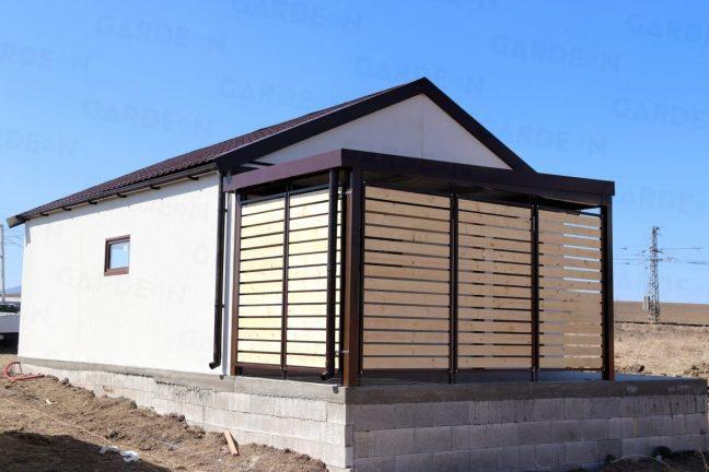 Eine Doppelgarage und eine Überdachung mit Wandelementen aus Holz