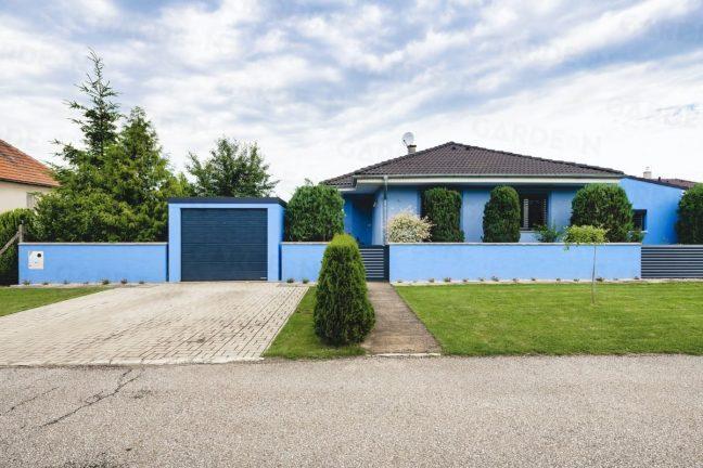 Eine blaue GARDEON Garage, angepasst an das Familienhaus