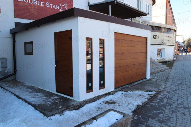 Eine montierte weiße Garage mit einer gedämmten Tür in der Farbe goldene Eiche