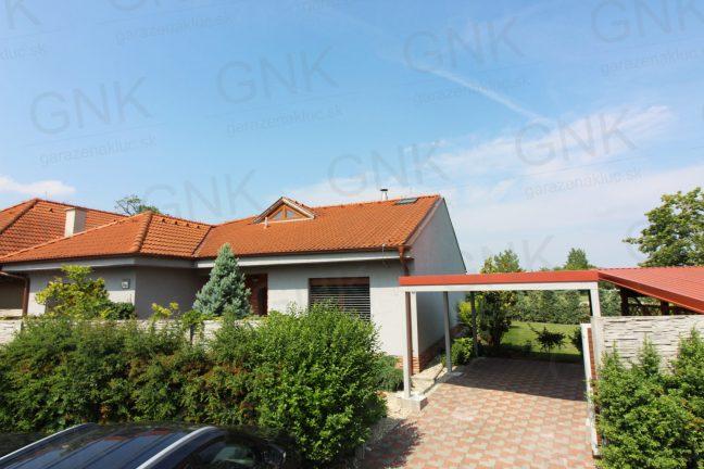 Ein montiertes Carport Standard mit einem Pultdach neben Familienhäusern mit Walmdächern