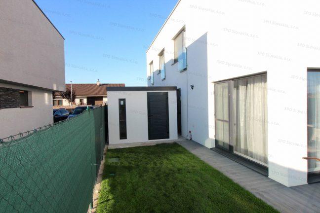 Ein Gartenhäuschen als ein Lagerraum bei einem Familienhaus in weiß