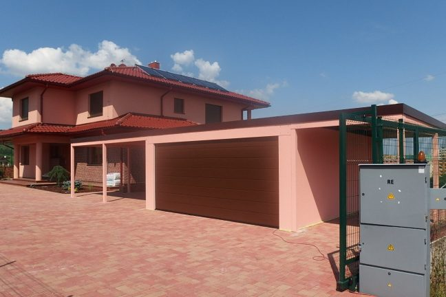 Eine Garage von GARDEON mit Überdachungen neben einem Haus mit atypischem Walmdach