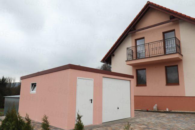 Eine atypische Garage in rosa vor einem Haus