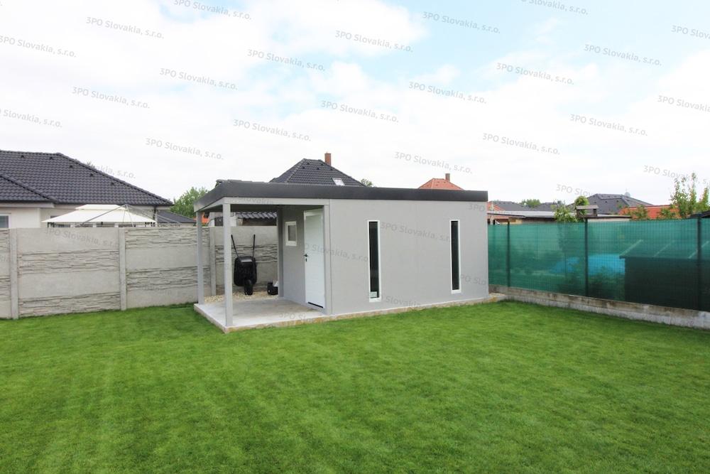 Ein licht-graues Gartenhaus in dem Garten