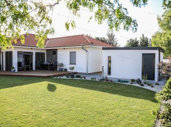 Ein modernes Häuschen von GARDEON auf einem Garten neben einem Familienhaus