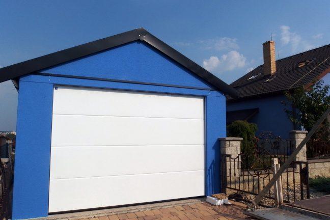 Eine moderne blaue Garage mit Satteldach und einem weißen Tor