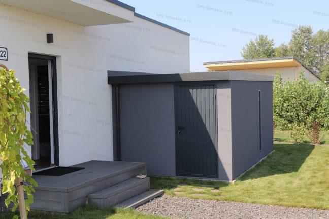 Ein modernes Gartenhaus in dunkel-grau bei einem weißen Familienhaus