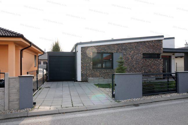 Eine montierte Garage in dunkel-grau mit einem Tor in anthrazit bei einem Familienhaus