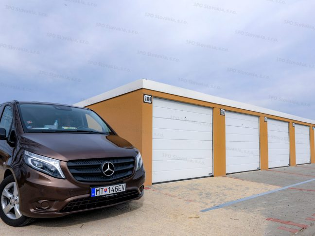 Reihengaragen in dunkel-gelb für 7 Autos mit Attika in weiß und Toren von Hörmann