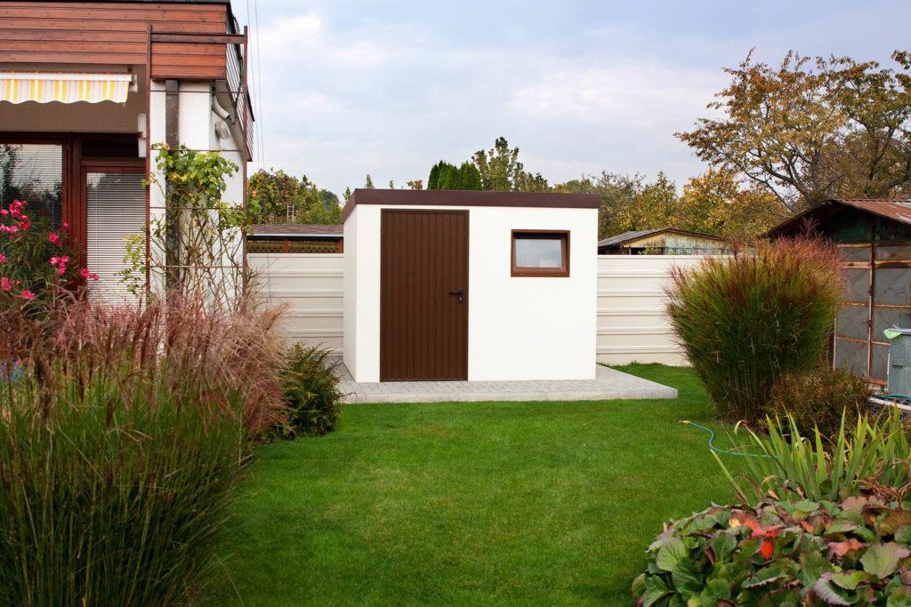 Ein Gartenhaus in weißer Farbe mit der Tür in braun