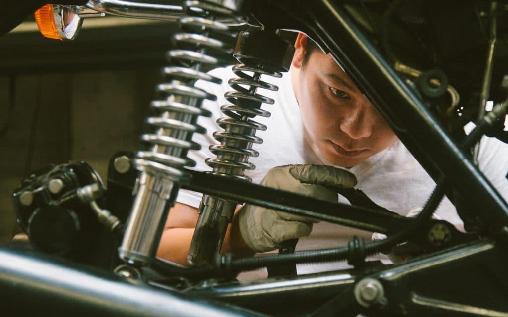 Ein Reparateur kuckt sich das Motorrad an