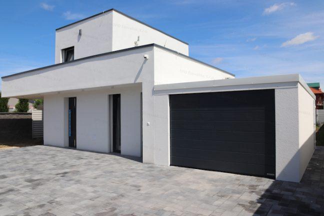 Eine montierte Garage mit weißem Putz und Attika, das Tor von Hörmann in anthrazit