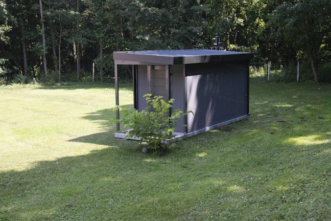 Ein Gartenhaus in dunkel-grau mit dunklem Zubehör