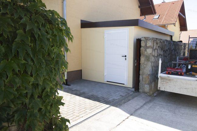 Ein Häuschen in licht-gelb mit einer weißen Tür und Attika in braun