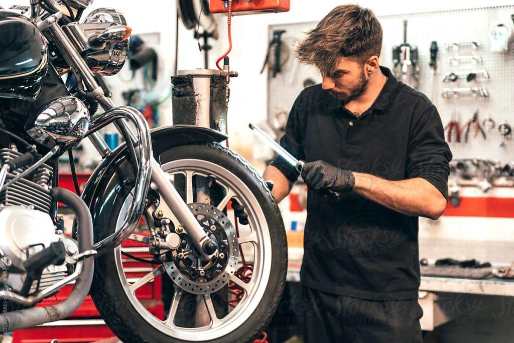 Ein Mann repariert sein Motorrad