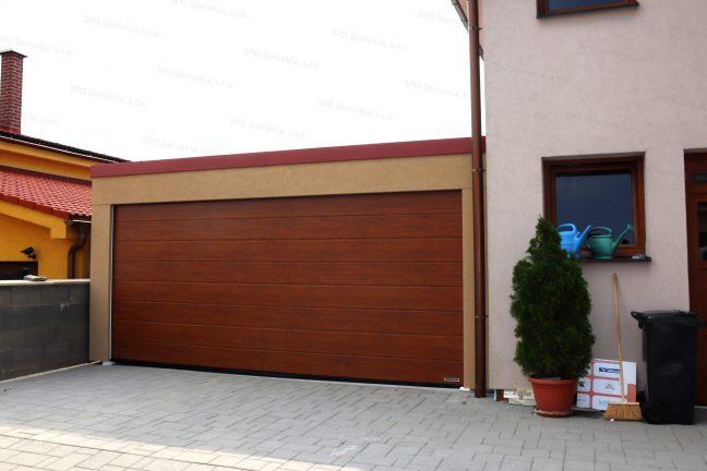 Eine Doppelgarage in beige mit der Attika in rot bei einem Familienhaus