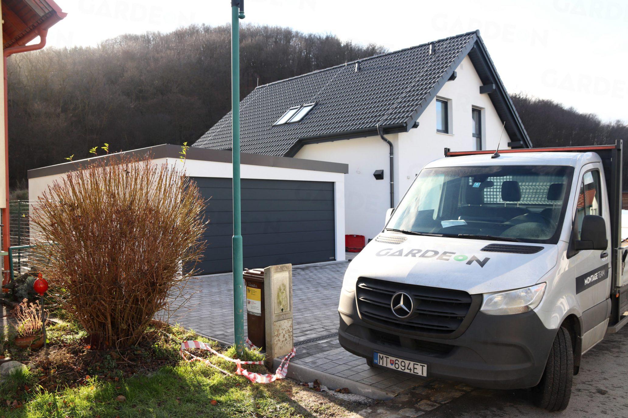 Eine montierte Doppelgarage von GARDEON bei einem Familienhaus mit Satteldach