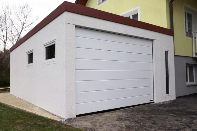 Eine weiße Garage mit einem weißen Tor von Hörmann