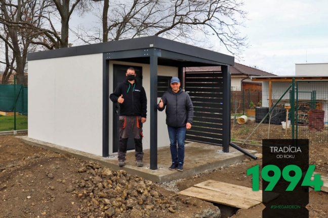 Ein zufriedener GARDEON Kunde vor seiner neuen Gartenhütte mit Überdachung