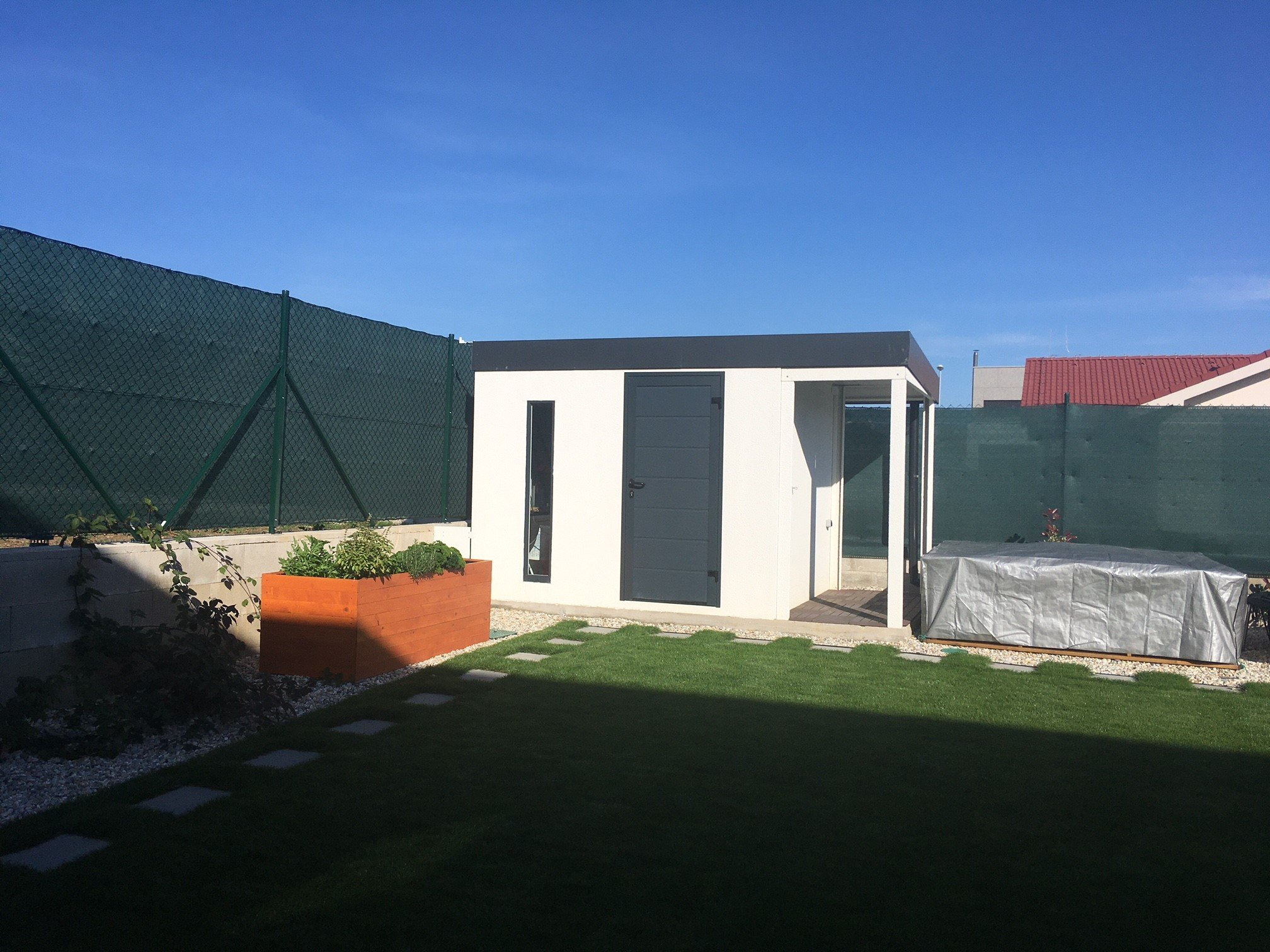 Ein weißes, montiertes Gartenhaus von GARDEON
