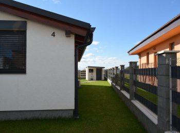 Das Gartenhäuschen von GARDEON mit Pultdach neben einem Haus mit Satteldach