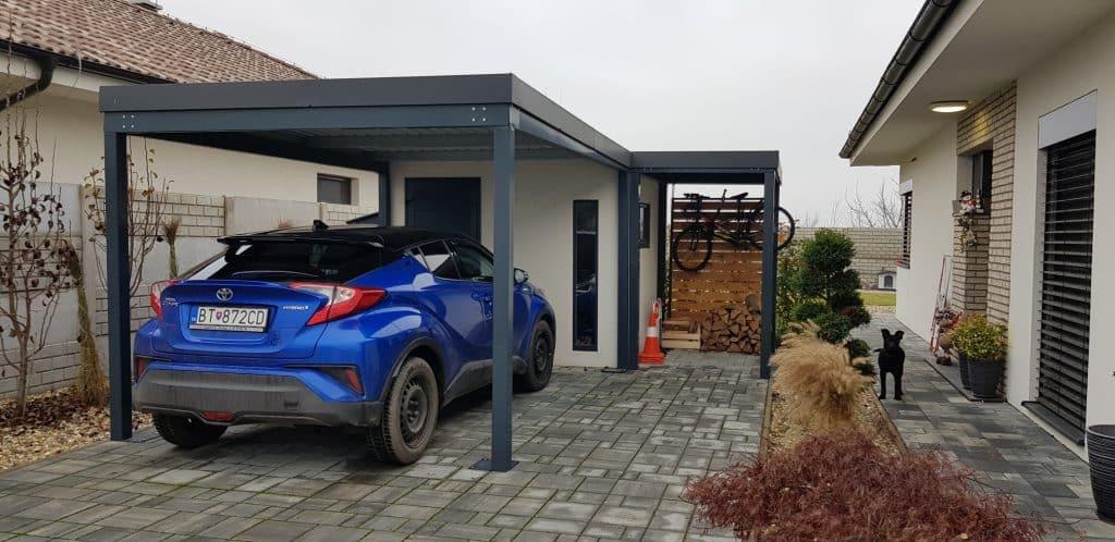 Auto geparkt unter einer Überdachung neben einer Gartenhütte