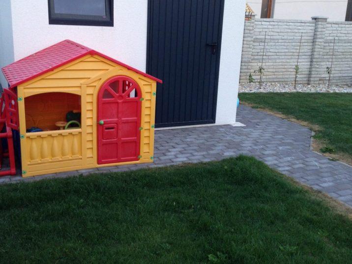 Eine kleine Gartenhütte aus Kunststoff neben dem Gartenhaus GARDEON