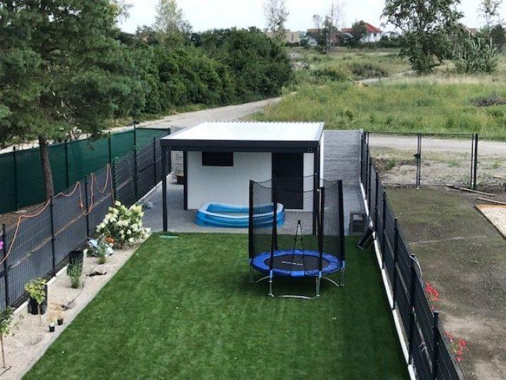Gartenhütte GARDEON mit einer Überdachung und einem Trampolin