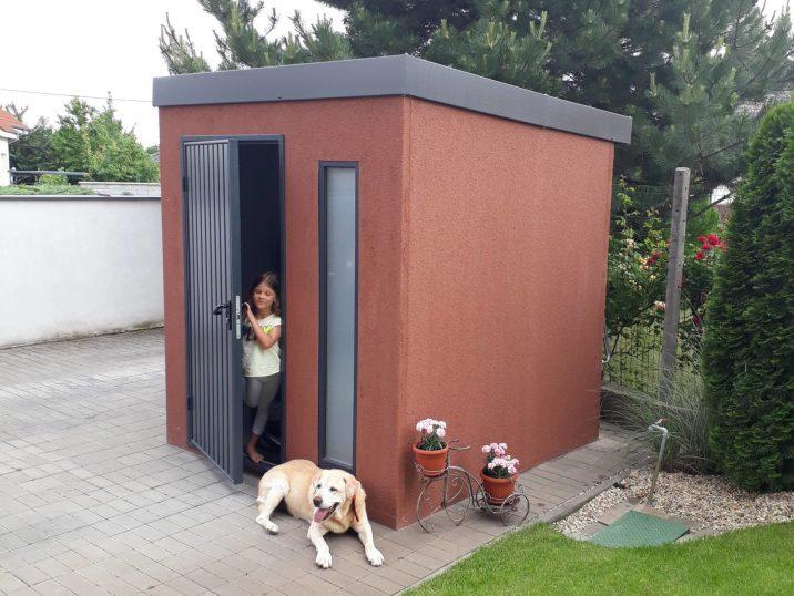 Braune Gartenhütte mit einer kleine Fräulein und dem Familienhund