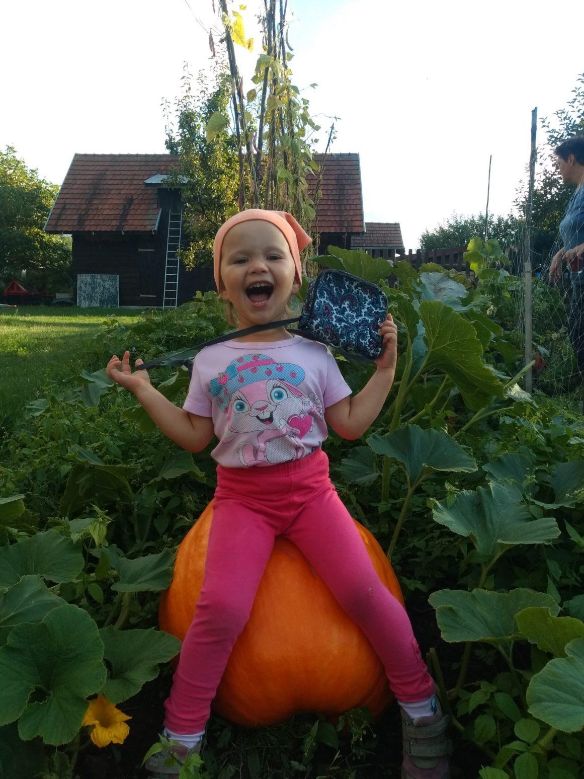 Ein lächelndes Mädchen sitz auf einem riesigen Kürbis