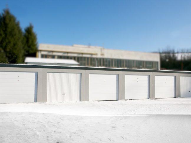 Reihengaragen mit Pultdach und weißen Toren