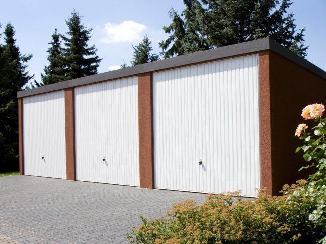 Eine Tripple-Garage mit weißen Schwingtoren