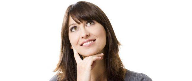 Eine Frau im grauen T-Shirt denkt nach