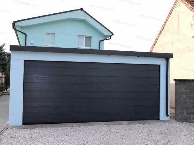 Eine montierte Garage mit Putz in der Farbe Menthol und einem Sektionaltor von Hörmann