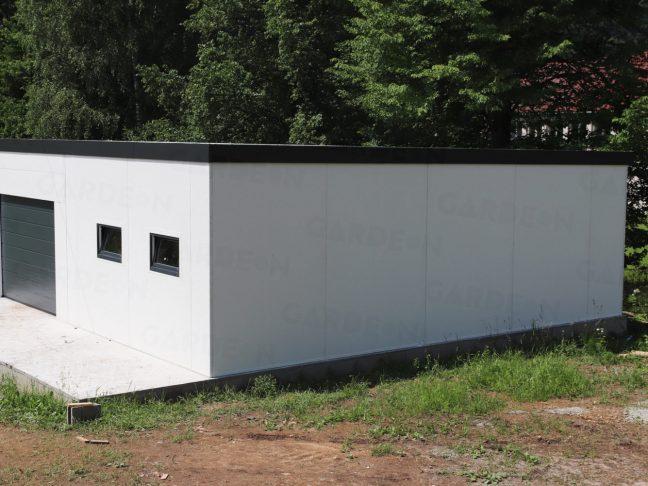 Ein montierter Lagerraum aus Stahl in weiß mit einem Tor in anthrazit