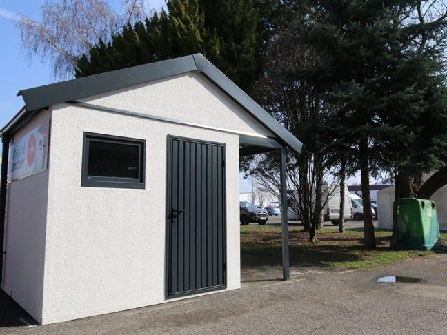 Ein Gartenhäuschen mit Satteldach und Überdachung rechts