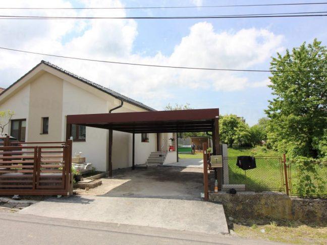 Ein braunes Doppelcarport von GARDEON bei einem Familienhaus mit Satteldach