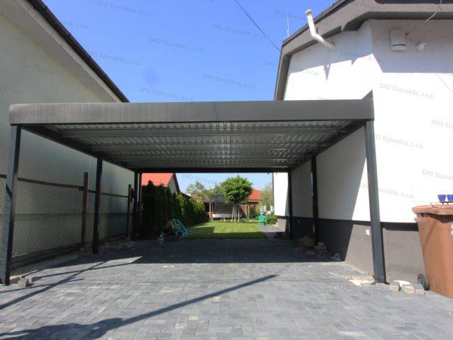 Das montierte Doppelcarport von GARDEON mit einem Flachdach neben eines Hauses mit Satteldach