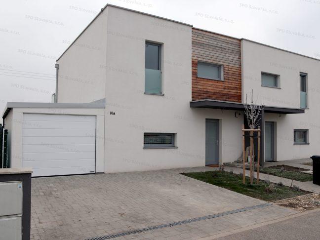 Eine montierte Einzelgarage in weiß neben einem Familienhaus