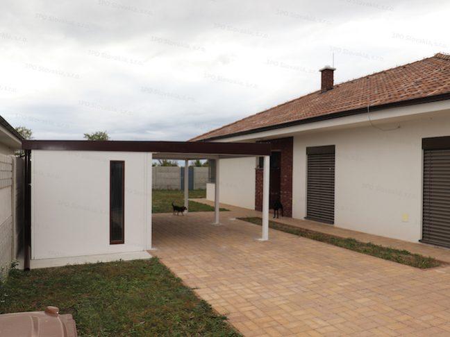 Ein montiertes Häuschen von GARDEON mit Überdachung beim Familienhaus