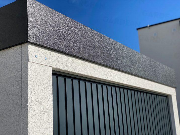 Die dunkel-graue Attika an einem montierten Bauwerk