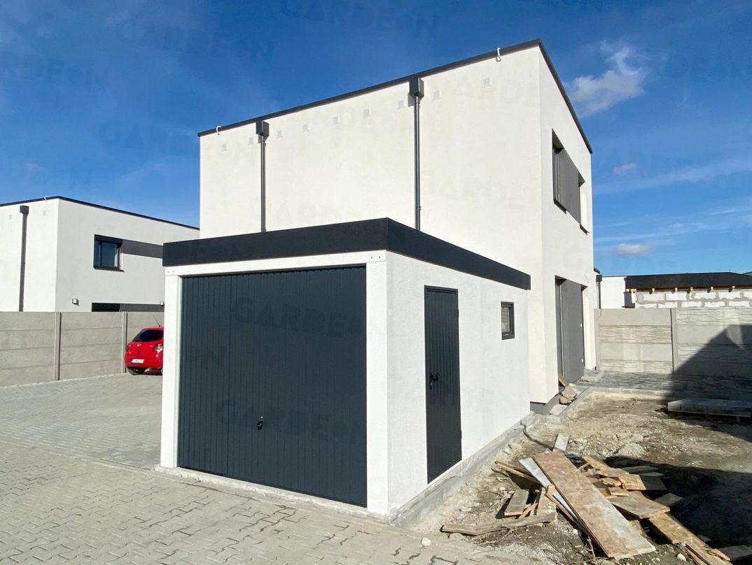 Eine Garage mit weißem Verputz und Dach in anthrazit