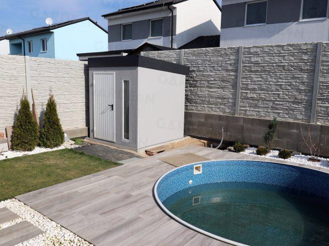 Ein Gartenhäuschen mit grauen Putz beim Pool