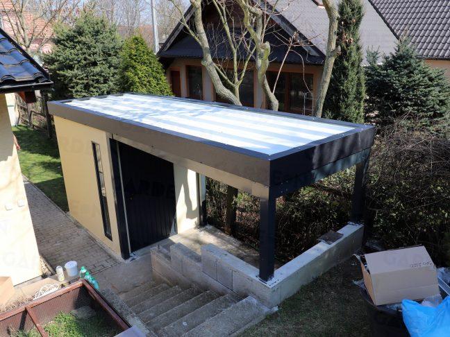 Ein Gartenhaus mit einer Überdachung an seiner rechten Seite