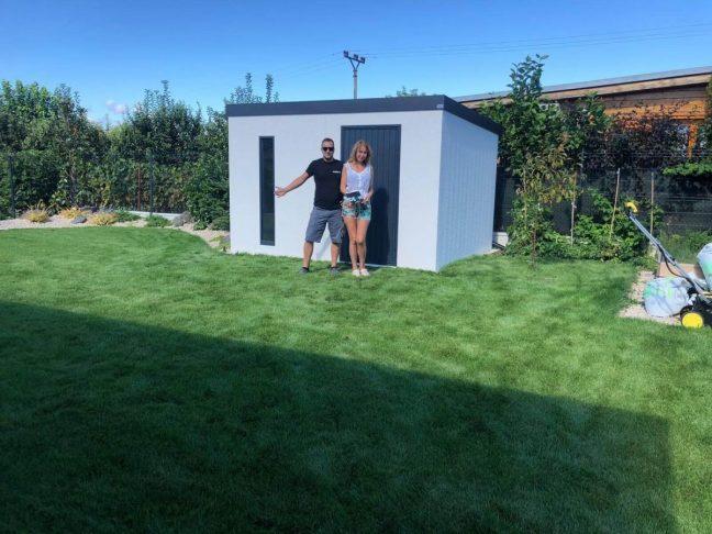 Eine zufrieden Kundin vor Ihrem neuen Gartenhaus