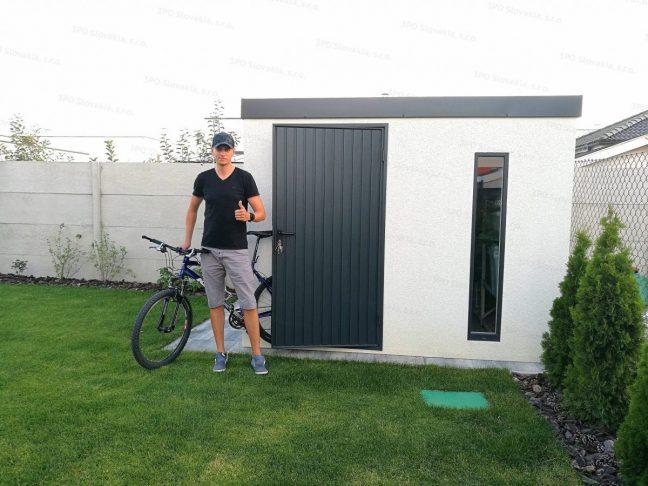 Ein zufriedener Kunden mit dem Fahrrad vor dem neuen Gartenhaus von GARDEON